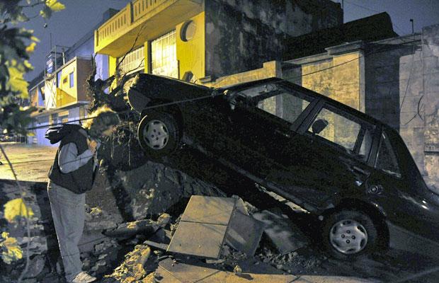 Homem observa automóvel destruído sobre calçada em Buenos Aires, nesta quinta (5) (Foto: AP)