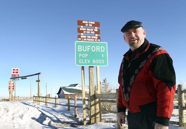 Sammons posa em 1º de janeiro deste ano em frente à placa registrando a população da cidade: 1 habitante (Foto: AP/Michael Smith/Wyoming Tribune Eagle)