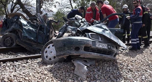 Equipes de resgate trabalham no que sobrou de carro atingido por trem nesta sexta-feira (6) em Kryoneri, na periferia norte de Atenas (Foto: Michail Michailidis/AP)
