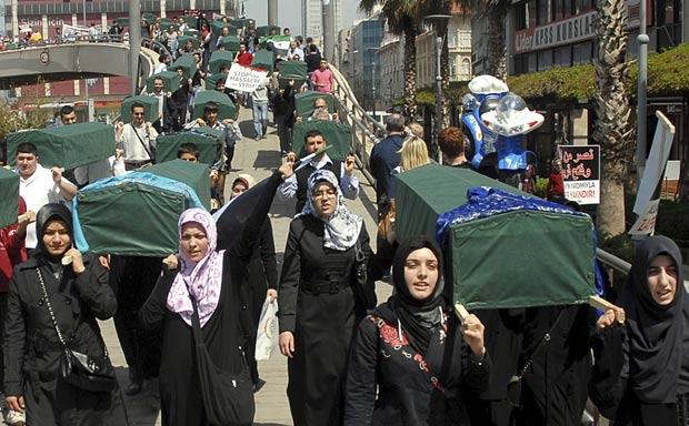 Sírios carregam caixões durante protesto contra Bashar al-Assad, neste sábado, em Izmir. (Foto: Reuters)