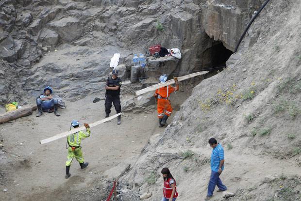 Mineiros levam toras de madeira para reforçar a estrutura da mina Cabeza de Negro, na cidade peruana de Ica, nesta segunda-feira (9) (Foto: Reuters)