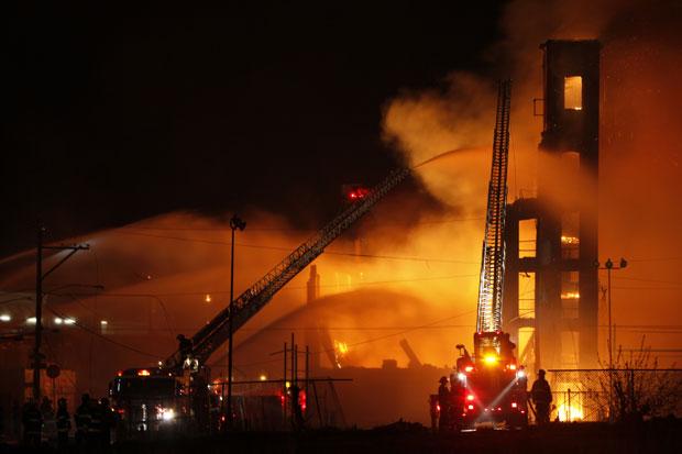 Um incêndio que tomou conta de um galpão na Filadélfia, no estado americano da Pensilvânia, deixou ao menos dois mortos na madrugada. Segundo as autoridades, as vítimas são dois homens que ajudavam a controlar o fogo de um prédio quando uma parede cedeu e os esmagou. (Foto: Joseph Kaczmarek/AP)