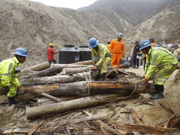 Operários usam toras para reforçar túnel (Foto: Martin Mejia/AP)