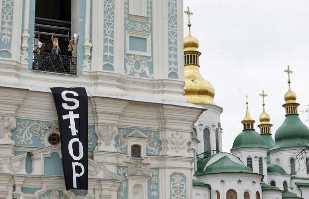 Nas placas se lê: 'crianças, igreja, cozinha' e 'eu não farei o parto por você' (Foto: Gleb Garanich/Reuters)