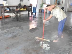 Proprietário de oficina teve que limpar a oficina após o local ser invadido por água (Foto: Aliny Mary Dias/G1 MS)