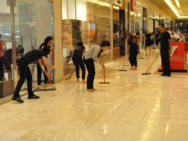 Funcionários de lojas limparam o corredor do shopping depois da água invadir o local (Foto: Aliny Mary Dias/G1MS)