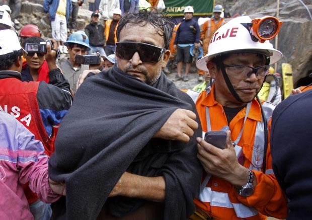 Homem é retirado com um cobertor e óculos escuros após seis dias soterrado (Foto: Martin Mejia/AP)