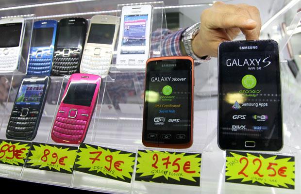 Vendedor exibe celulares da Samsung e da Nokia em loja em Bruxelas (Foto: Francois Lenoir/Reuters)
