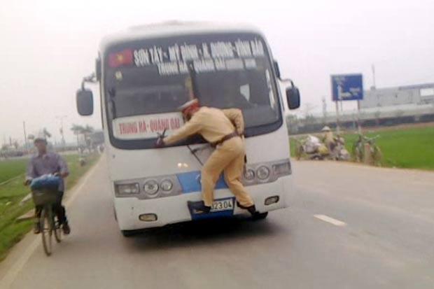 Policial andou por quase um quilômetro pendurado na frente de um ônibus. (Foto: AP)