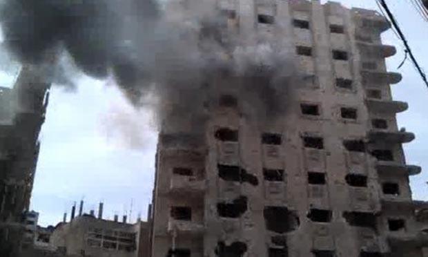 Imagem de vídeo amador mostra prédio que estaria sendo bombardeado neste sábado (14) na cidade síria de Homs (Foto: AP)