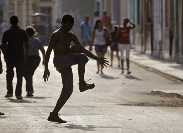 Garoto joga bola em rua de Havana, capital de Cuba, nesta quinta-feira (12) (Foto: AP)