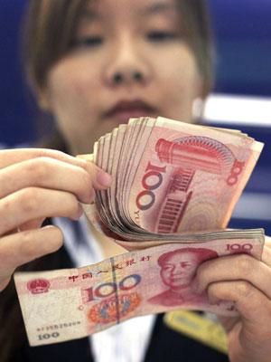 Bancária conta notas de iuan na China em foto de arquivo de 2010. A partir de segunda-feira, governo permite maior oscilação da moeda sobre o dólar (Foto: AP)