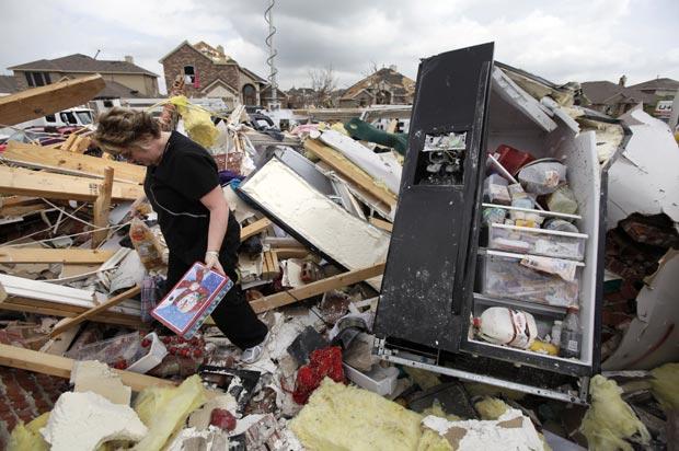 Ashley Quinton anda entre os destroços da casa de sua amiga Sherry Enochs na tentativa de salvar ben, neste sábado (14), na cidade texana de Forney (Foto: AP)