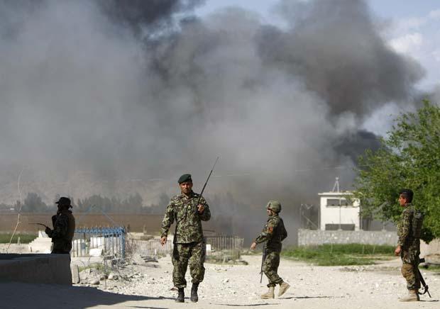 Soldados movimentam-se em meio a fumaça provocada por ataque talibã à cidade afegã de Jalalabad neste domingo (15) (Foto: Reuters)
