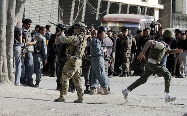 Soldado da Otan monta guarda em um dos locais atacados neste domingo (15) em Cabul, capital do Afeganistão (Foto: AP)