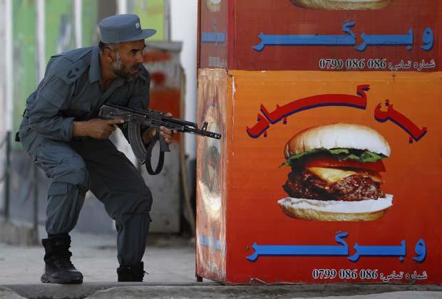 Policial afegão durante tiroteio neste domingo (15) em Cabul (Foto: Reuters)