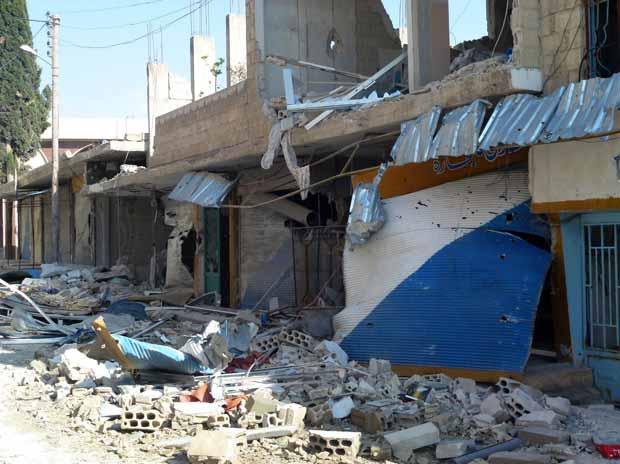 Estragos que, segundo a oposição, teria sido provocados por bombardeios do Exército sírio a Qusayr, a 15 quilômetros de Homs, neste sábado (14) (Foto: AFP)