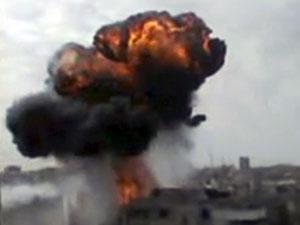 Imagem de vídeo amador acessada neste domingo (15) mostra fumaça em borbardeio em Homs (Foto: AP Photo/Shaam News Network via AP video)