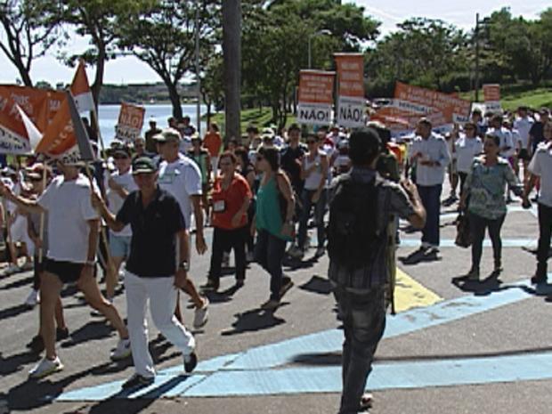 Manifestantes fazem passeata na orla da Lagoa da Pampulha contra construção de hotéis. (Foto: Reprodução TV Globo)