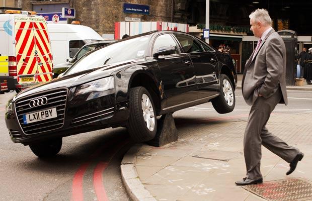 Um motorista ficou com o carro suspenso ao 'montar' sobre um bloqueador de tráfego. (Foto: Leon Neal/AFP)