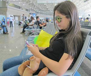 A capixaba Alessandra Freire conseguiu acessar a internet por seu celular no Galeão (Foto: G1)