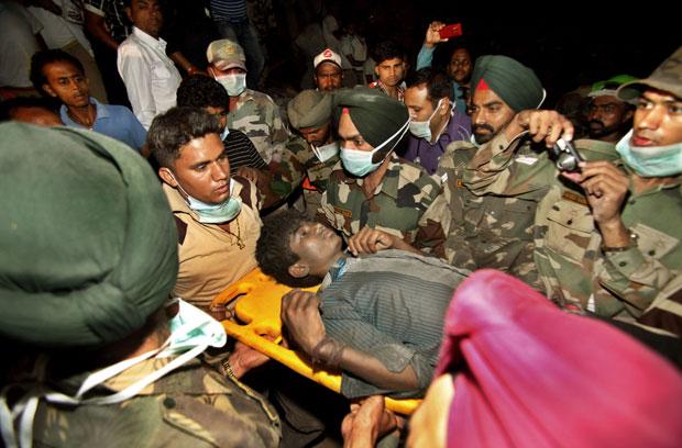 O garoto Sandeep é resgatado nesta quarta-feira (18) na cidade indiana de Jalandhar (Foto: AP)