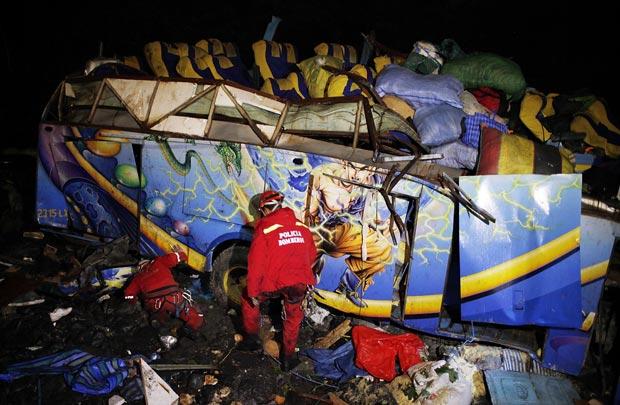 Bombeiros trabalham nos destroços do ônibus acidentado nesta quinta-feira (19) na Bolívia (Foto: AFP)