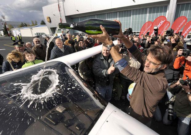 O biólogo celebra jogando champagne sobre o avião (Foto: Srdjan Zivulovic/Reuters)
