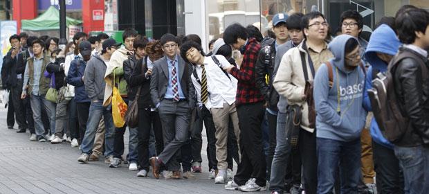 Consumidores esperam na fila em frente à loja da Apple em Seul, na Coreia do Sul (Foto: Lee Jin-man/AP)