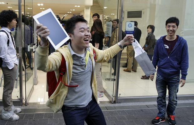 Baek Sung-min, de 23 anos, comemora a compra do novo iPad em loja da Apple em Seul, na Coreia do Sul (Foto: Lee Jin-man/AP)