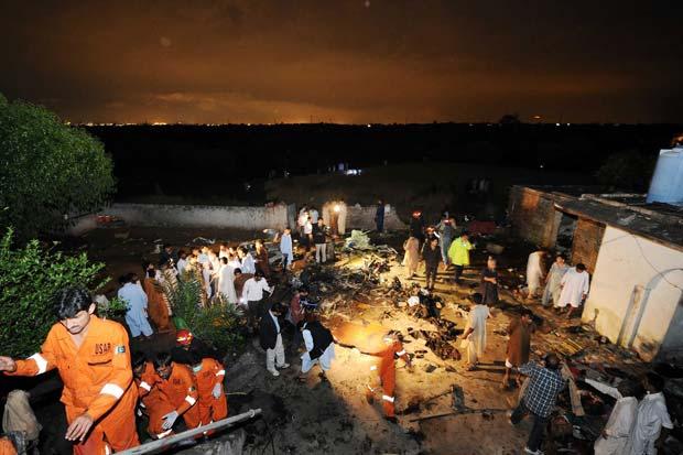 Equipes de resgate e moradores no local da queda do avião nesta sexta-feira (20) no Paquistão (Foto: AFP)