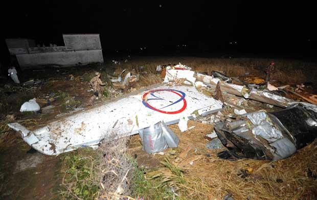 Resgatistas cercam o que sobrou da asa do avião acidentado nesta sexta-feira (20) (Foto: AFP)