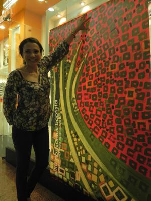 """Júlia Baptista ao lado de um dos painéis da série """"Brasília 50"""" (Foto: Káthia Mello/G1)"""