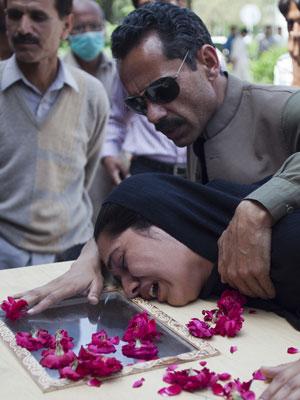 Homem conforta mulher que chora sobre o caixão de familiar morto no acidente aéreo, em hospital de Islamabad (Foto: B.K. Bangash/AP)