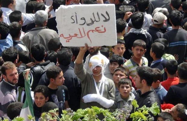 Manifestantes protestam em Talbiseh contra o regime do presidente Bashar al Assad após as rezas de sexta-feira (20). No cartaz, lê-se: 'Não aos medicamentos. Sim à liberdade' (Foto: Reuters)