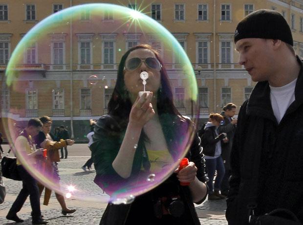 Participante faz bolha em festival de bolhas de sabão que ocorreu em praça de São Petersburgo (Foto: Alexander Demianchuk/Reuters)