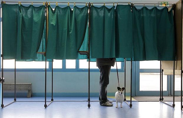 Eleitor francês vota em cabine de Henin-Beaumont, norte do país, neste domingo (22) (Foto: Jacques Brinon/AP)