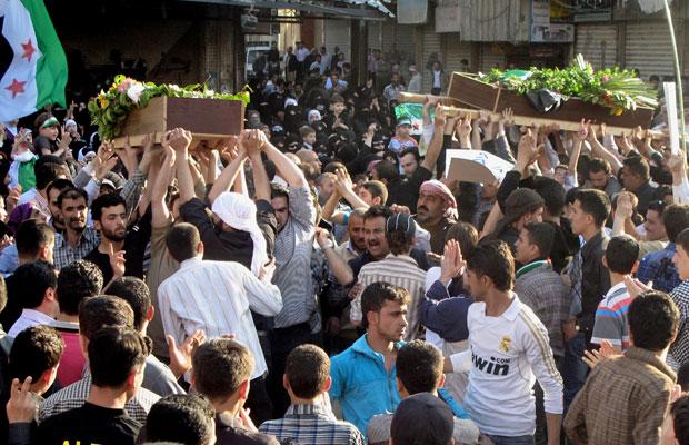 Imagem deste sábado (21) mostra caixões de uma criança e de um guerrilheiro do Exército Livre da Síria sendo levados em funeral no subúrbio de Damasco (Foto: AP)