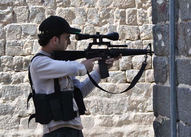 Rebelde faz mira durante confronto em Homs neste domingo (22), em foto divulgada pela oposição (Foto: AP)