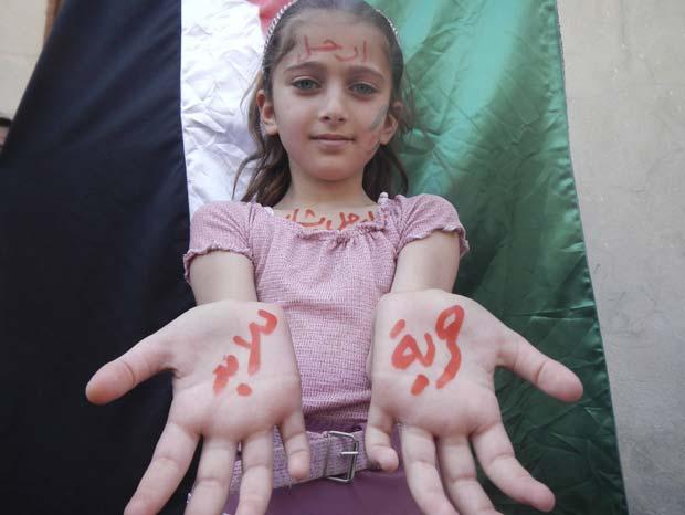 Menina participa de protesto contra o governo da Síria nesta quarta-feira (25) em Kafranbel, próximo a Idlib. Nas suas palmas, está escrito, em árabe, 'liberdade para sempre' (Foto: Raad Al Fares/Shaam News Network/Reuters)