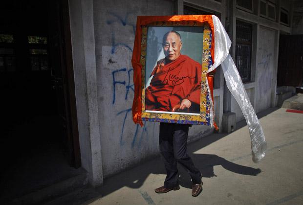 Tibetano carrega retrato do líder espiritual Dalai Lama em Katmandu, no Nepal, nesta quarta-feira (5) (Foto: Niranjan Shrestha/AP)