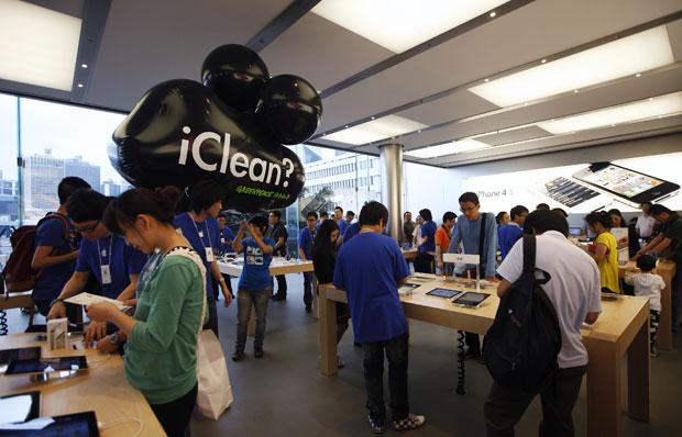 Manifestantes do grupo Greenpeace levaram balões para uma loja da Apple em Hong Kong protestando contra o fato de a empresa não usar fontes renováveis e limpas em seus produtos. Os balões bricam com o nome dos produtos da companhia com a palavra 'iClrean' (Foto: Tyrone Siu/Reuters)