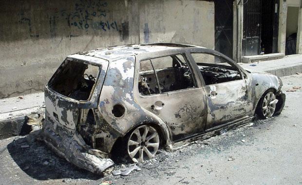 Carro destruído é visto em rua de Homs, na Síria, no dia 24 (Foto: Reuters)