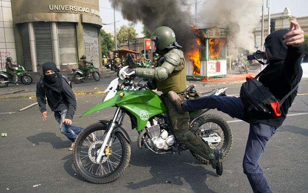 Manifestantes entram em confronto com a polícia nas ruas de Santiago (Foto: AFP)
