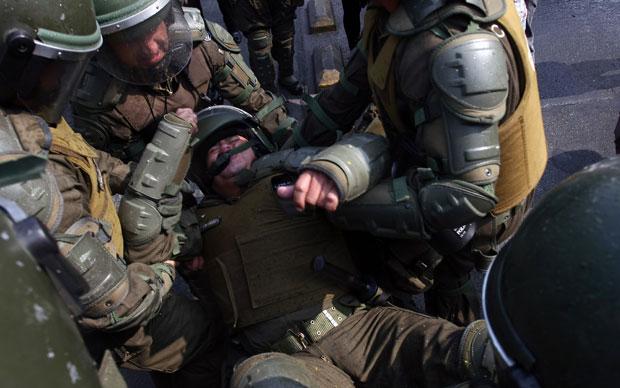 Policial é socorrido por colegas após ficar ferido em confronto (Foto: AFP)
