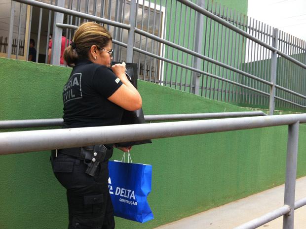 Policial chega à Divisão Especial de Repressão ao Crime Organizado (Deco) com sacola da Delta Construção (Foto: Natalia Godoy / G1)