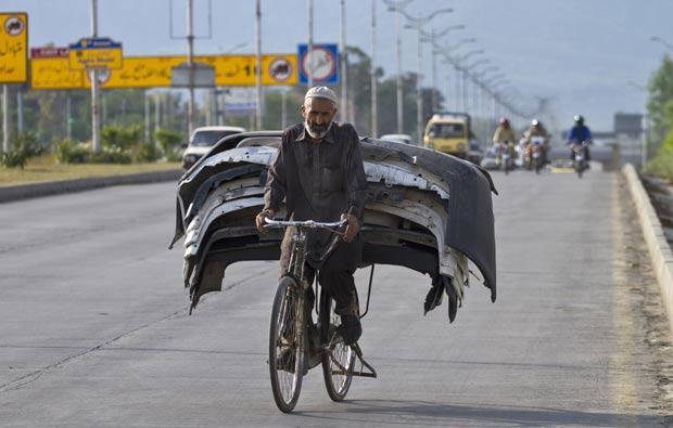 Um paquistanês foi flagrado transportando por vários para-choques na garupa de sua bicicleta em uma estrada em Islamabad, no Paquistão.  (Foto: Anjum Naveed/AP)