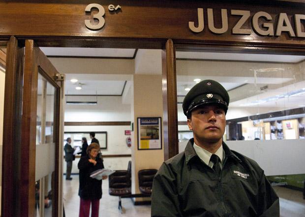 Policial monta guarda em frente a tribunal em Santiago durante a abertura do testamento de Pinochet nesta quarta-feira (25) (Foto: AFP)