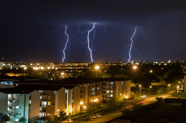 O fotógrafo Luis Robayo conseguiu registrar o momento em que três raios atingem o solo durante tempestade na quarta-feira (25) em Cali, na Colômbia. (Foto: AFP)