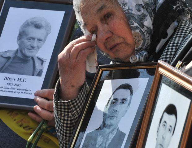 Viúva mostra foto de seu marido, morto no acidente nuclear de Chernobyl, durante ato em memória às vítimas em Kiev nesta quinta-feira (26) (Foto: Sergei Supinsky/AFP)